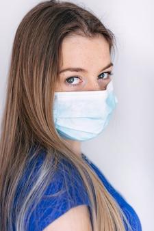 Mooie maar trieste vrouw met medische masker op gezicht. de vrouw is verdrietig omdat ze bang is voor moderne virussen die ziekten veroorzaken. het medische masker waarschuwt voor virussen