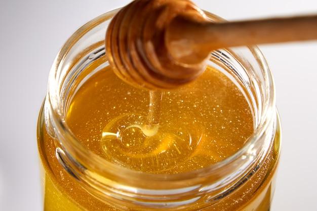 Mooie macro opname van honing in een pot van bovenaf. smakelijke gouden druppel honing met een gestructureerde textuur