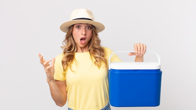 Mooie magere vrouw die extreem geschokt en verrast is en een zomerpicknickkoelkast vasthoudt