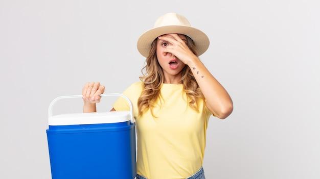 Mooie magere vrouw die geschokt, bang of doodsbang kijkt, haar gezicht bedekt met de hand en een zomerpicknickkoelkast vasthoudt