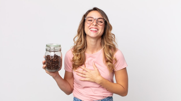 Mooie magere vrouw die hardop lacht om een hilarische grap en een fles koffiebonen vasthoudt