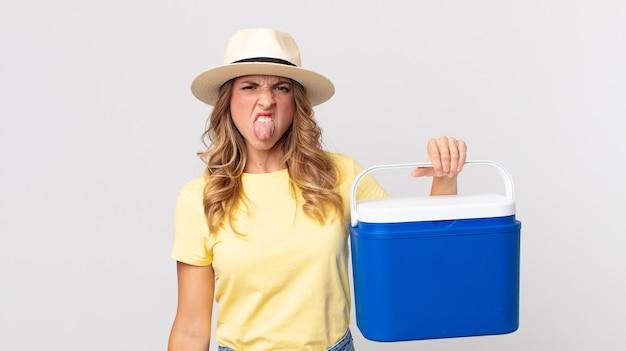 Mooie magere vrouw die walgt en geïrriteerd voelt en haar tong uitsteekt en een zomerpicknickkoelkast vasthoudt