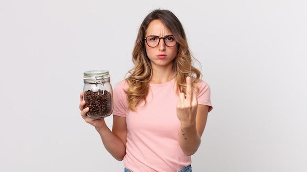 Mooie magere vrouw die zich boos, geïrriteerd, opstandig en agressief voelt en een fles koffiebonen vasthoudt