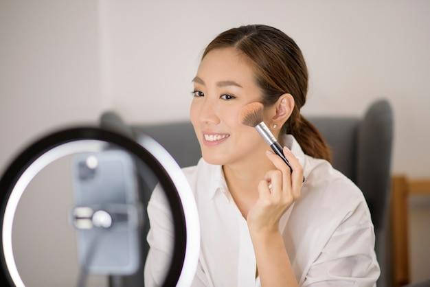 Mooie make-up blogger streamt live hoe ze gezichtsmake-up in haar huis kan gebruiken