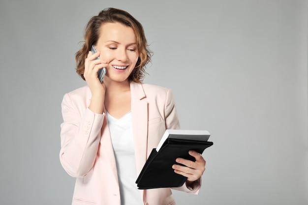 Mooie makelaar in onroerend goed praten via de telefoon
