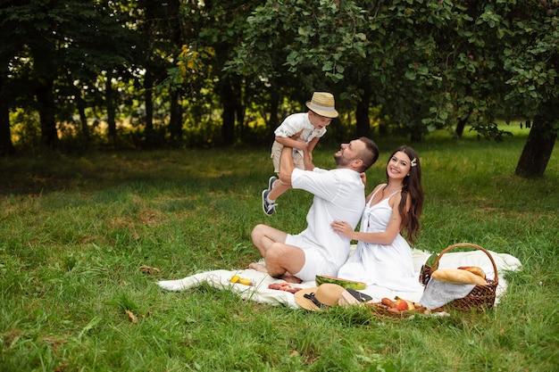 Mooie mama, papa en hun schattige kleine kind hebben samen plezier en glimlachen buiten