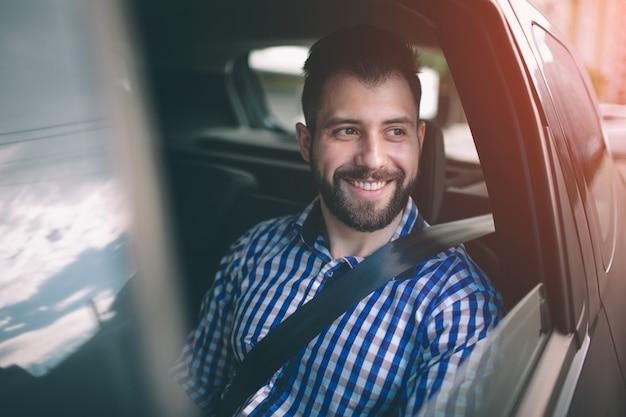 Mooie man die lacht zittend op de achterbank in de auto