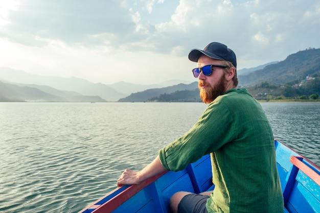 Mooie man in een boot op een meer op de achtergrond van bergen. het concept van buitenactiviteiten en toerisme in de natuur. wandelen in de himalaya in nepal