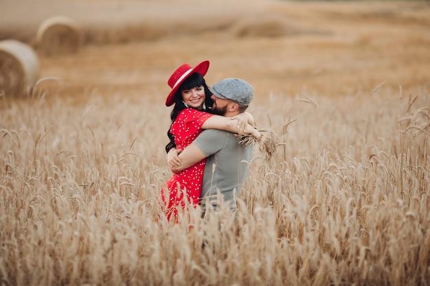 Mooie man in grijs t-shirt, hoed en korte broek houdt mooie blanke vrouw met lang donker golvend haar in rode jurk met bloemen op zijn handen