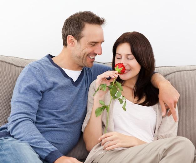Mooie man kijkt naar zijn vriendin ruiken een rode roos