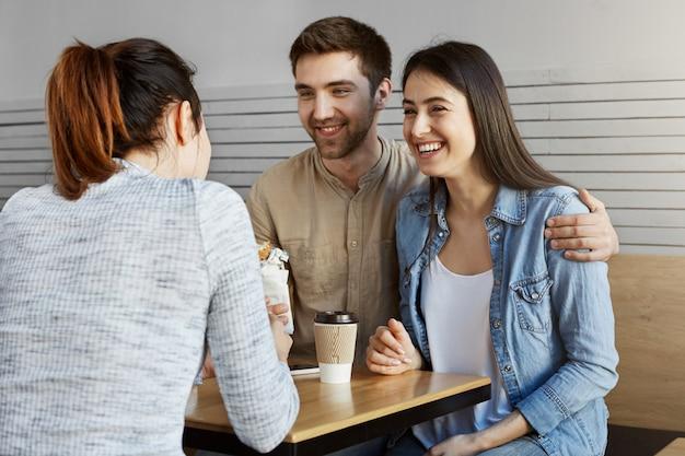 Mooie man met donker haar stelt zijn vriendin voor aan vriend, ze lachen, eten sandwiches, hebben plezier samen.