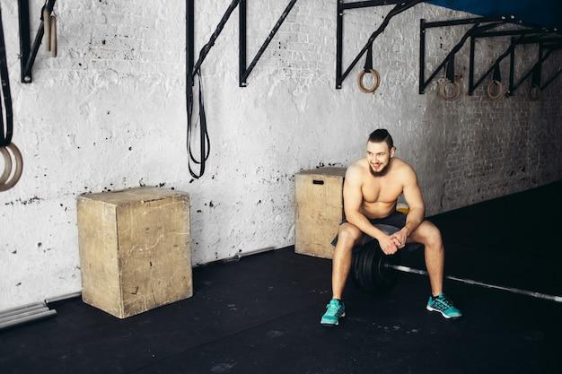 Mooie man moe na gewichtheffen op sportschool