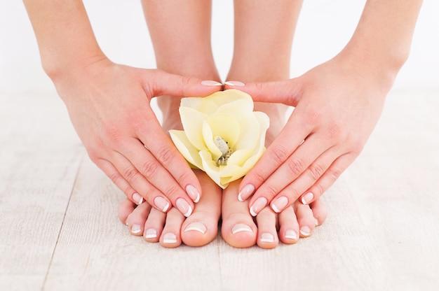 Mooie manicure en pedicure. close-up van een jonge vrouw die haar voeten aanraakt terwijl ze op een hardhouten vloer staat