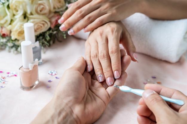 Mooie manicure nagels verf met glitter en edelstenen in nagelsalon