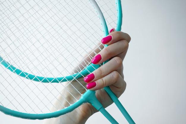 Mooie manicure. schoonheid en sport concept. mooie vrouwelijke hand houdt een badmintonracket op een witte achtergrond.