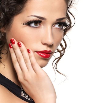 Mooie maniervrouw met rode manicure en lippen