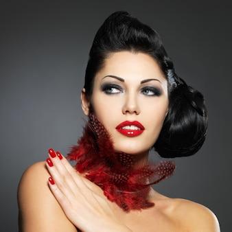 Mooie maniervrouw met rode spijkers, creatief kapsel en make-up - model poseren
