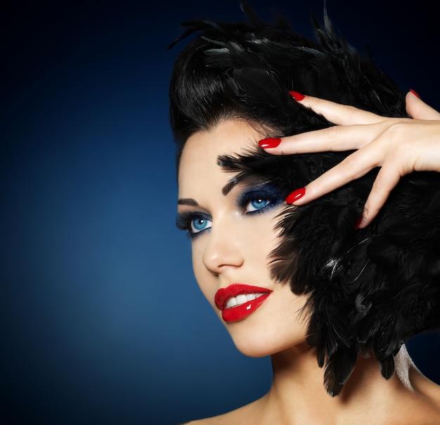 Mooie maniervrouw met rode spijkers, creatief kapsel en make-up