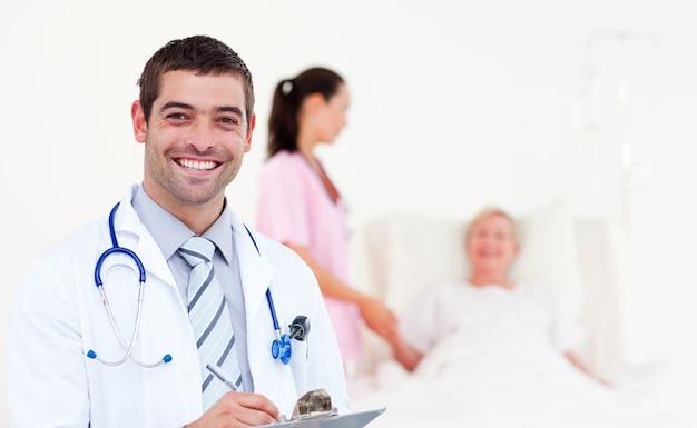 Mooie mannelijke arts die zijn diagnose schrijft