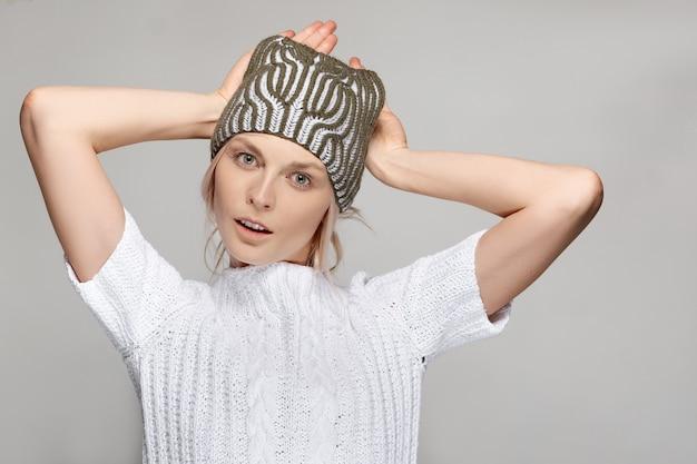 Mooie mannequin in witte trui en gebreide muts houdt handen achter haar hoofd