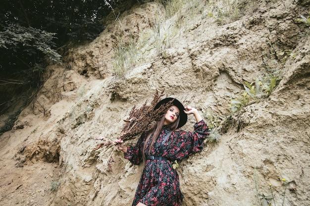 Mooie mannequinvrouw met make-up en kostuum buiten op de achtergrond van zand
