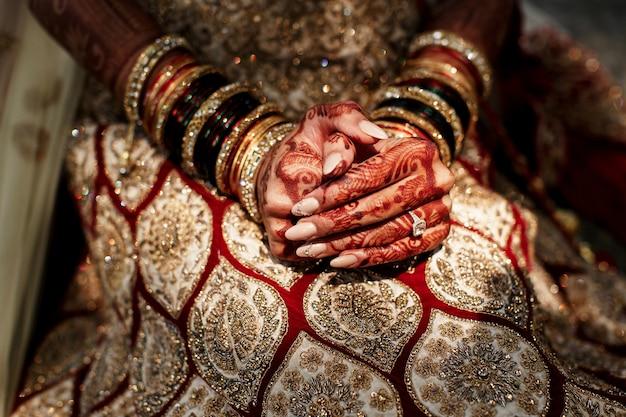 Mooie mehndi-patronen bedekken de vingers van de bruid die ze vasthoudt