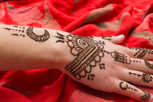 Mooie mehnditatoegering op vrouwenhand die op rode textiel wordt geplaatst