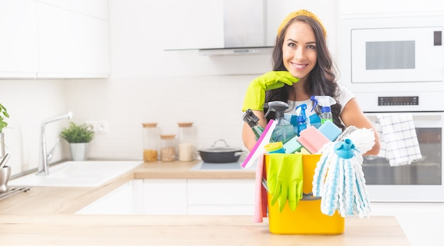 Mooie meid die in de keuken staat, met een emmer vol kleurrijke schoonmaakspullen voor haar, met rubberen handschoenen in de camera kijkend.