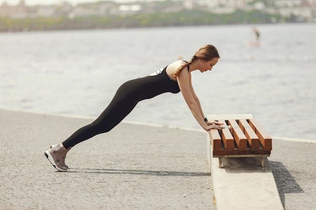 Mooie meid opleiding. sport meisje in een sportkleding. vrouw aan het water.
