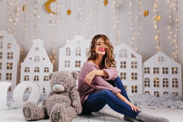 Mooie meid van 25 jaar oud zit op de vloer met haar teddy speeltje over een witte muur met warme decoraties zoals heldere, gouden sterren