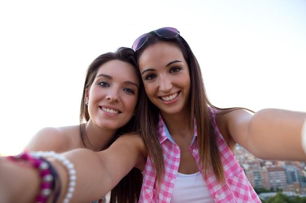 Mooie meiden nemen een selfie op het dak bij zonsondergang.