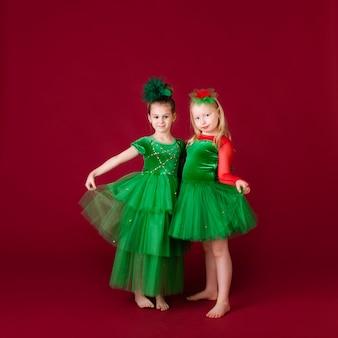 Mooie meisjeprinsessen die in luxe groene kleding dansen die op rode muur wordt geïsoleerd. carnaval feest met kostuums