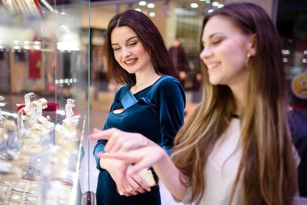 Mooie meisjes die boodschappen doen in de mall.