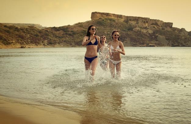Mooie meisjes die in de zee lopen