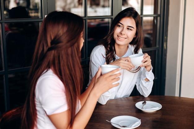 Mooie meisjes die koffie drinken tijdens een bedrijfslunch in een koffie