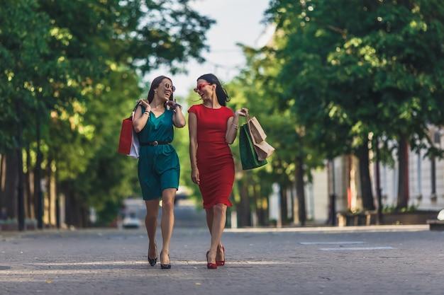 Mooie meisjes die met het winkelen zakken bij de straat van de de zomerstad lopen. s