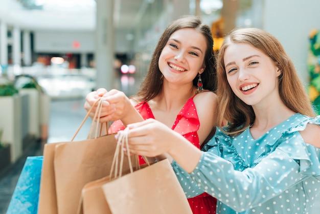 Mooie meisjes die met het winkelen zakken stellen