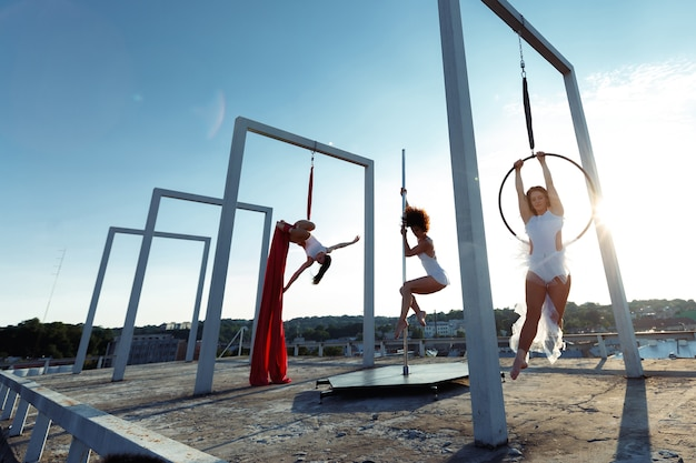 Mooie meisjes die pool, lucht en hoepeldans op dak uitvoeren