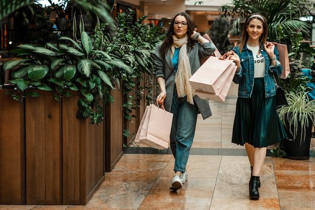 Mooie meisjes doen aankopen in een winkelcentrum, gaan winkelen.