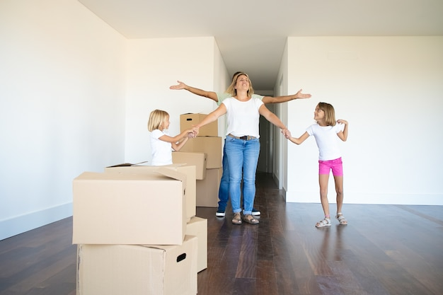 Mooie meisjes en hun vader laten hun nieuwe flat zien aan een gelukkige moeder