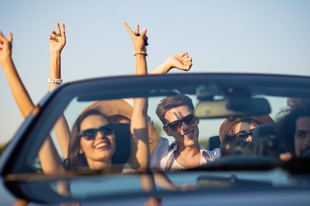 Mooie meisjes en jongens in zonnebrillen glimlachen en rijden in een zwarte cabriolet op de weg met hun handen omhoog op een zonnige dag. .