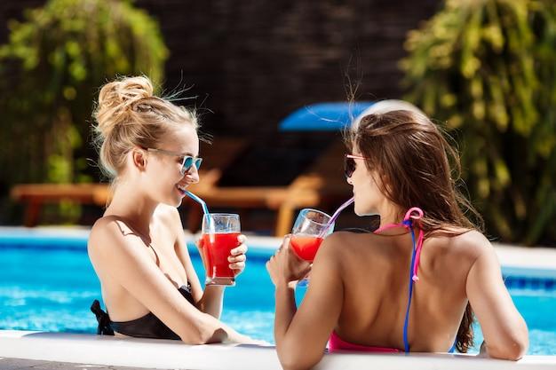 Mooie meisjes glimlachen, spreken, cocktails drinken, ontspannen in het zwembad.