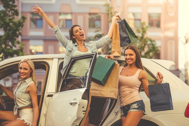 Mooie meisjes gluren uit een auto met tassen
