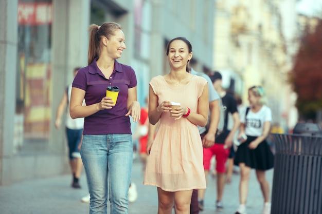 Mooie meisjes houden papieren koffiekopje en genieten van de wandeling in de stad op zonnige zomerdag. lifestyle-concept