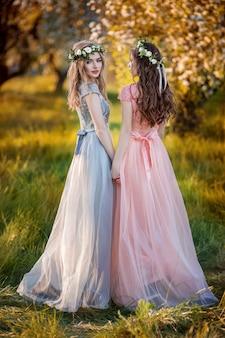 Mooie meisjes in een tuin van de bloemlente