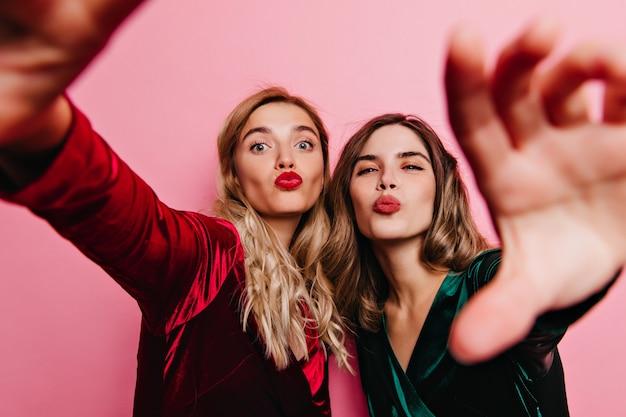 Mooie meisjes in fluwelen jurken poseren met kussende gezichtsuitdrukking. indoor shot van zorgeloze stijlvolle dames selfie maken.