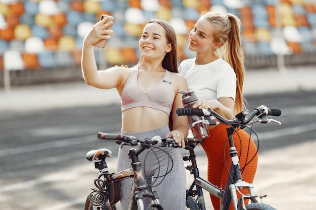 Mooie meisjes in het stadion. sportmeisjes in sportkleding. mensen met een fiets.