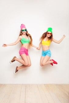 Mooie meisjes in hoeden en glazen die plezier hebben en springen