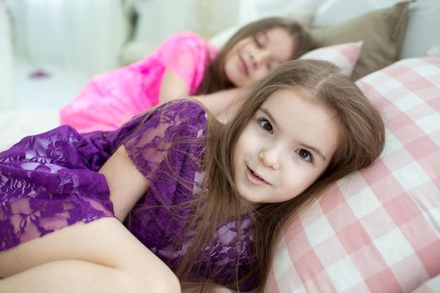Mooie meisjes in roze en paarse jurken in bed