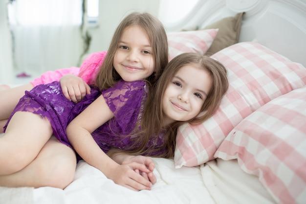 Mooie meisjes in roze en paarse jurken lagen in bed